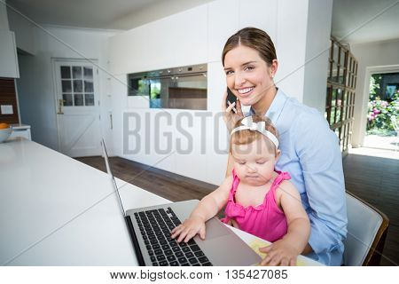 Happy woman using mobile phone while sitting with baby girl by laptop at home