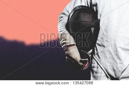 Mid-section of man standing with fencing mask against blurred mountains