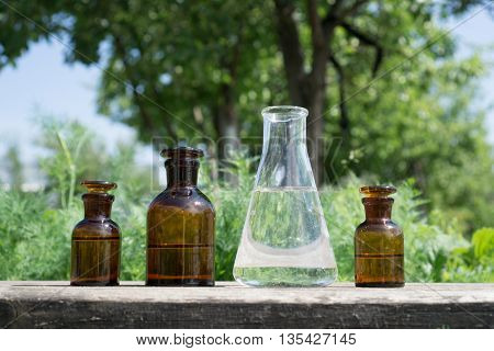 Liquid in chemical ware on a background of plants, fertilizers or pesticides in the garden.