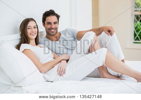 Portrait of happy couple resting on bed at home