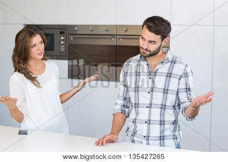 Woman explaining man while standing by table at home