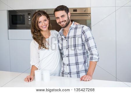 Portrait of happy young couple standing by table in kitchen at home