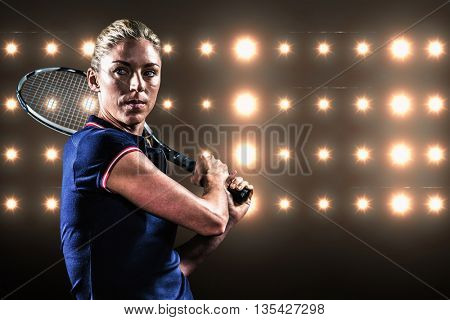 Tennis player playing tennis with a racket against composite image of orange spotlight