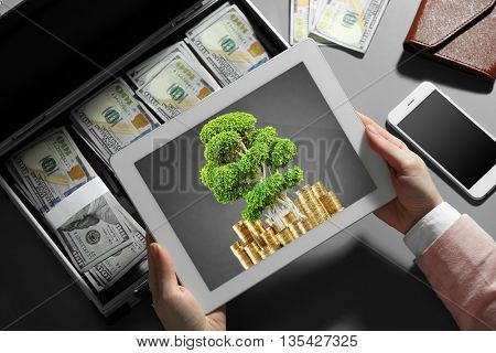 Businesswoman with green tree and coins on screen of tablet and case full of money