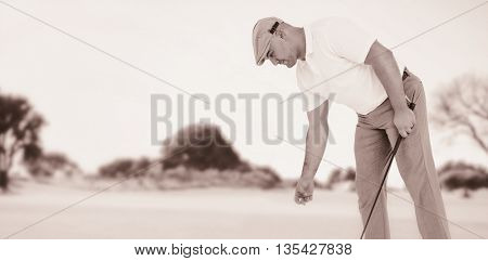 Golf player picking up golf ball against view of a park