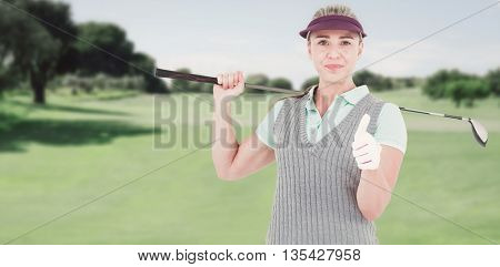 Pretty blonde playing golf and showing a thumbs up against view of a landscape