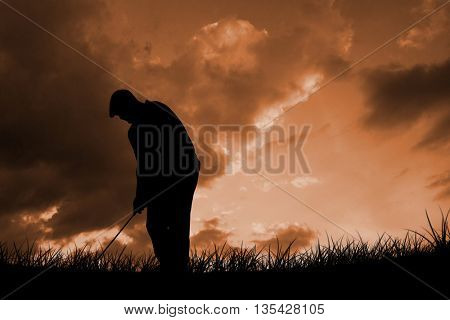 Golfplayer about to swing a golf ball against cloudy sky