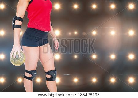 Female athlete with elbow pad holding handball against composite image of orange spotlight