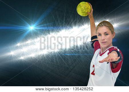 Sportswoman throwing a ball against spotlights