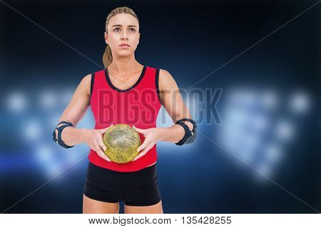 Female athlete with elbow pad holding handball against composite image of spotlight