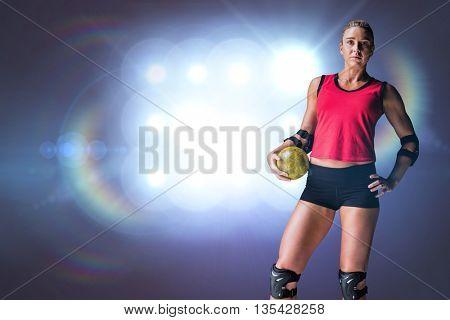 Female athlete with elbow pad holding handball against spotlights
