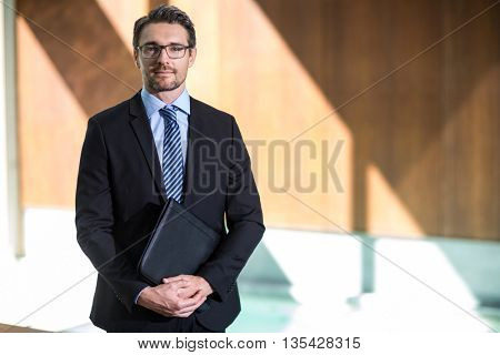 Portrait of businessman standing in resort with folder file in hand