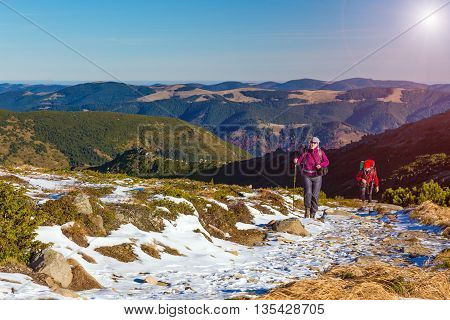 Hiker Climbs Up on Snowy Trail Towards High Mountain Ridge Carrying Backpacks Grass Blue Sky and Shining Sun