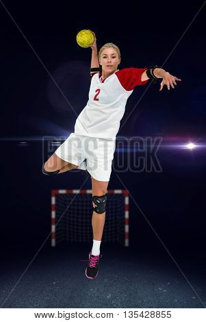 Sportswoman throwing a ball against view of lighting