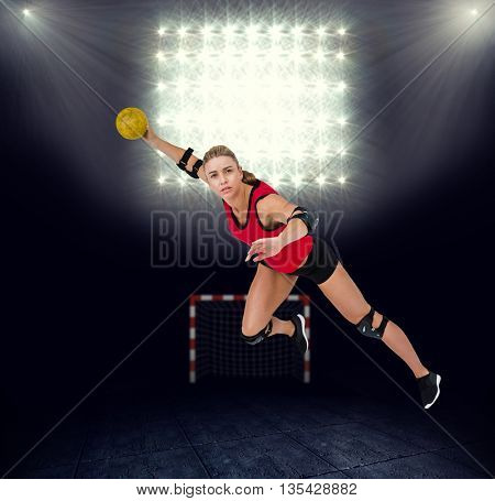 Female athlete throwing handball against view of spotlights