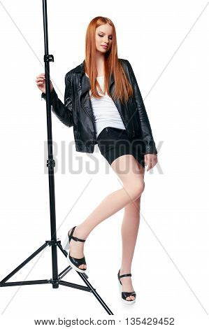 Gorgeous red haired fashion model in black leather jacket posing in studio with photo stand