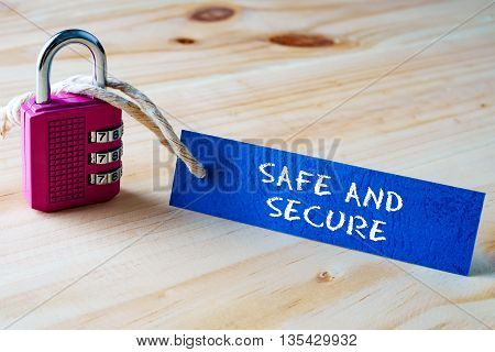 Words Safe And Secure Written On Tag Label Tied With A Padlock.