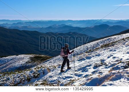 Female Athlete Sport Clothing carrying Backpack Walking Up Mountain Peaks Sunlight Sky Majestic Summits Background