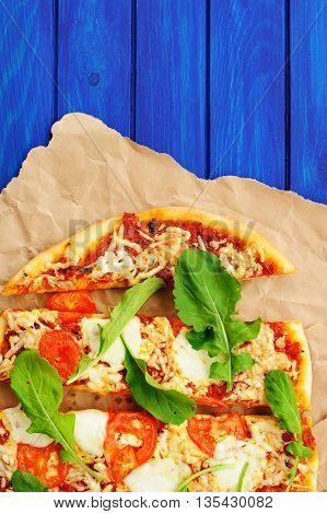 Rucola pizza on wrinkled craft paper with blue background with copyspace