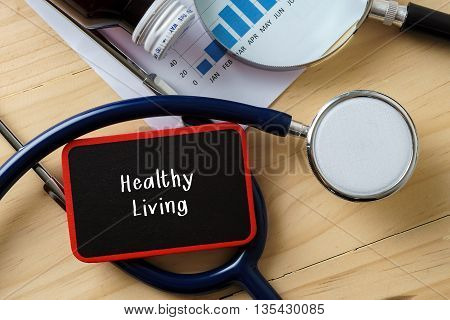 Medical Conceptual.stethoscope On Wooden Table With Word Healthy Living.