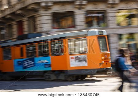 Milan Italy - May 04 2016: Color tram in motion on a street of Milan at spring time