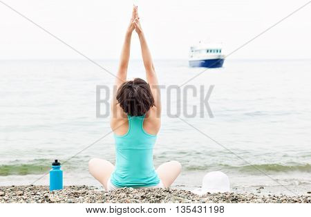 woman meditating in lotus yoga by the sea on the beach