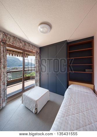 Interior of an old apartment, bedroom with single bed and closet