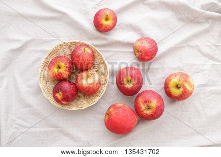 Apples fruit in basket and fabric on white background