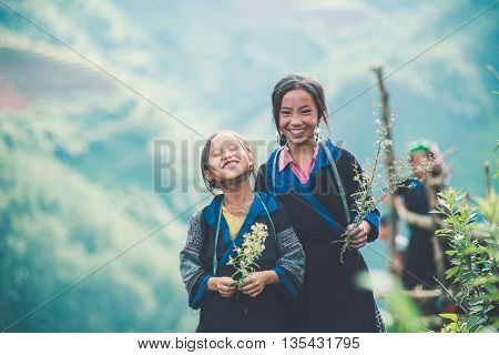 MUCANGCHAI, VIETNAM, JUNE 12, 2016: H'mong ethnic minority kids near terraced rice field in Mucangchai, Vietnam. H'mong is the 8th largest ethnic group in Vietnam.