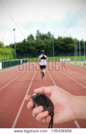 Close up of coach is holding a stopwatch against concentrated male sprinter training