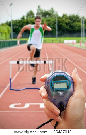Close up of woman is holding a stopwatch on a white background against sporty man jumping above hedge during a race