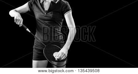 Badminton player holding a racquet ready to serve on black background