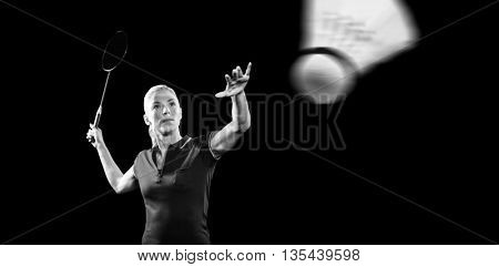 Badminton player playing badminton on black background