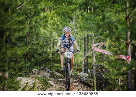 Kyshtym Russia - June 16 2016: young girl cyclist riding his bike on stones in spruce forest during Championship of Russia on mountain bike