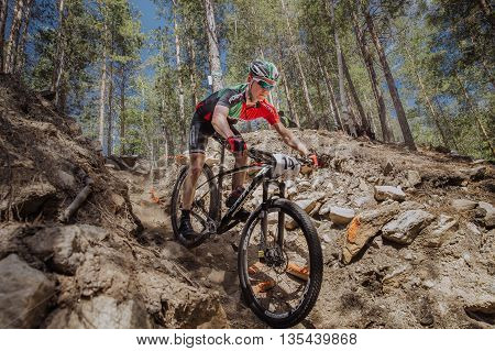 Kyshtym Russia - June 16 2016: male athlete cyclist going down a hill over stones during Championship of Russia on mountain bike