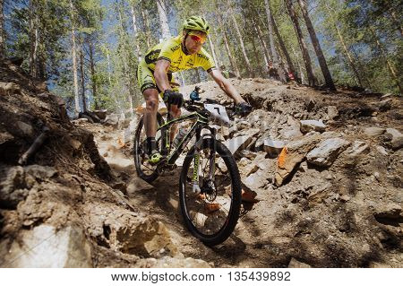 Kyshtym Russia - June 16 2016: male athlete cyclist rides down mountain on stones during Championship of Russia on mountain bike