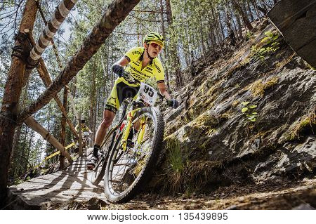 Kyshtym Russia - June 16 2016: closeup of man athlete cyclist rides down mountain a wooden bridge during Championship of Russia on mountain bike