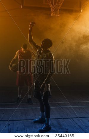 Victorious basketball player raising his arms up while his rival looking down
