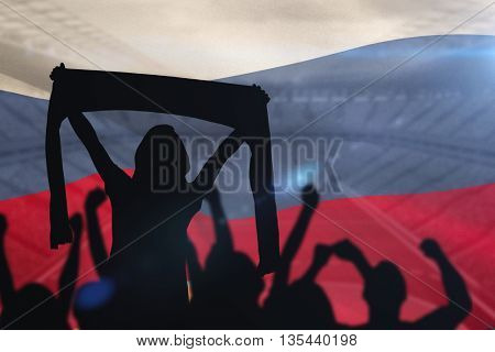 Silhouettes of football supporters against digitally generated russia national flag