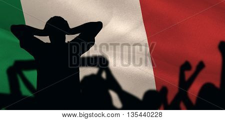 Silhouettes of football supporters against digitally generated italy national flag