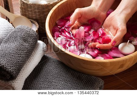 Female hands and bowl of spa water with flowers hand care in nail salon relaxing manicure with a pink rose flower