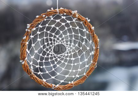 Handmade dream catcher on background of rocks and lake. Tribal elements feathers