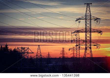 High-voltage electric line on a background of red sunset