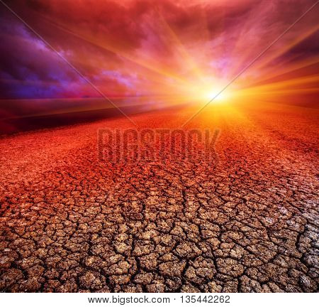 dramatic sunset scene over dry cracked earth