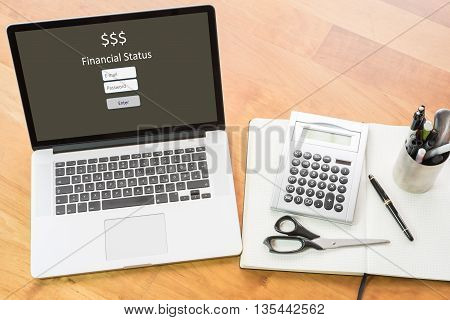 wooden desk with computer and notebook - login financial status