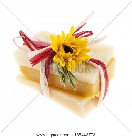 Several herbal handmade artisan soap pieces tied with fresh flowers isolated on white background