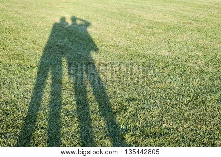 Long shadows of two people taking photos standing on grass lawn with copy space