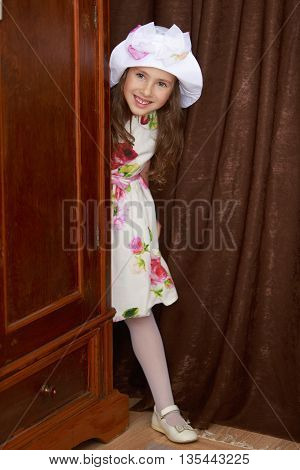 Cheerful little girl in a smart white dress with the roses peeping from behind the old Cabinet