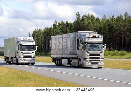 SALO FINLAND - JUNE 19 2016: Scania R490 cargo trucks overtakes another Scania truck R410 on motorway in on a clear day of summer in South of Finland.