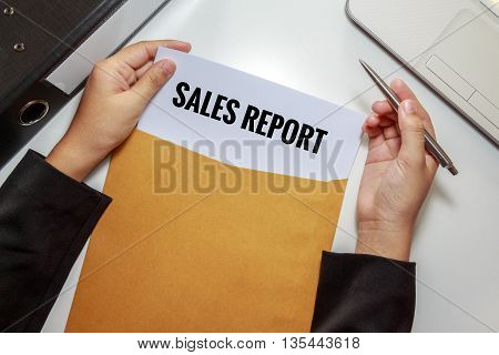 Businesswoman opening Sales Report document in letter envelope.